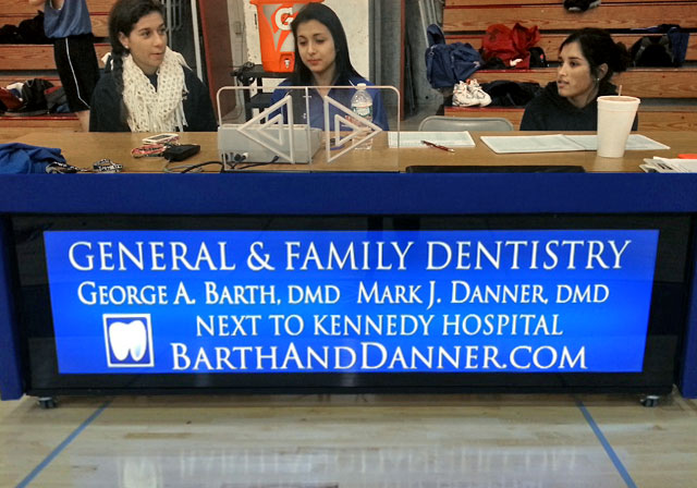 Barth and Danner score keeper's table sponsorship sign at the game